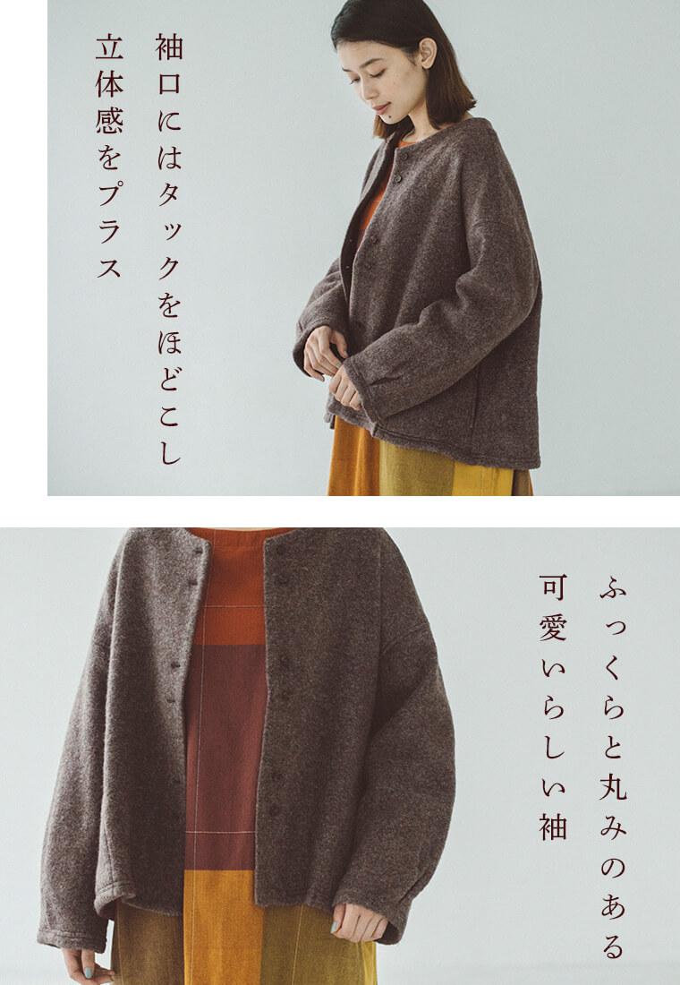 チャコールの羽織とチェックワンピースを着た下向いた女性