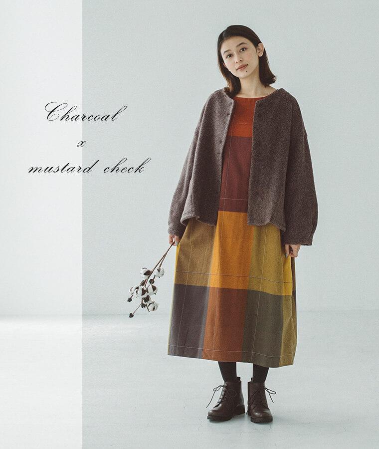 チャコールの羽織とチェックワンピースを着た女性