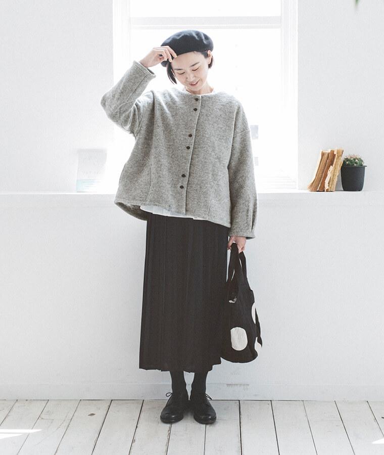 グレーの羽織とブラックワンピースを着た下向いた女性