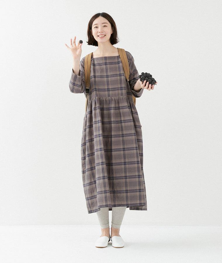 グレーのチェックワンピースを着てる女性