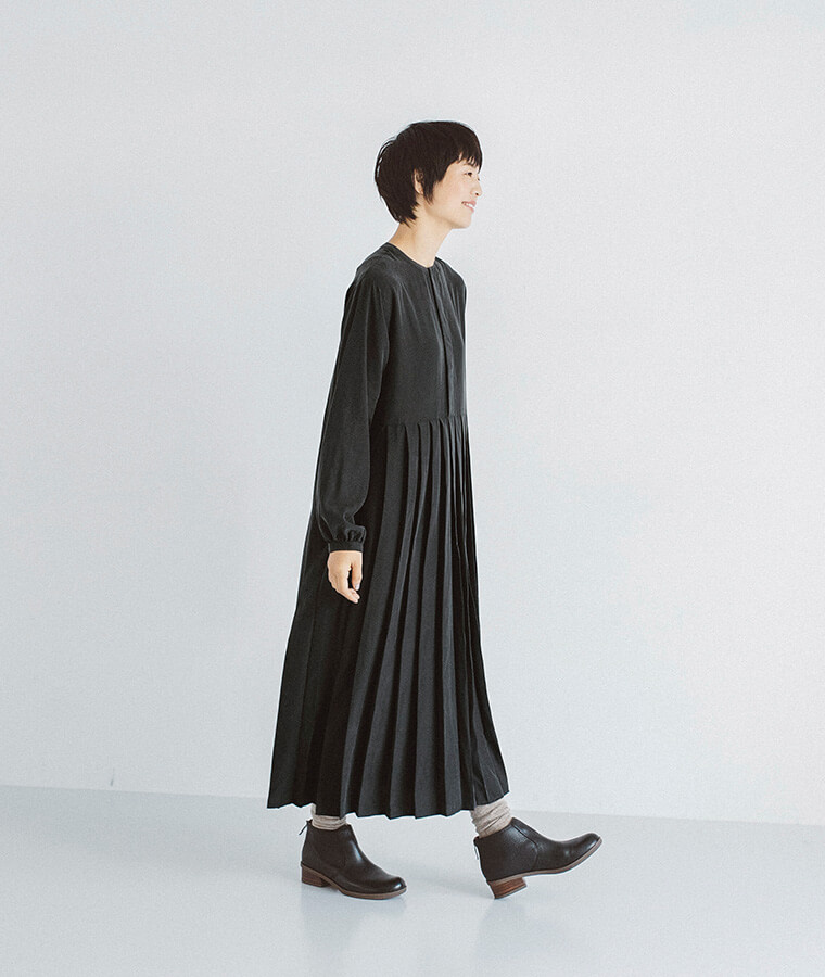 プリーツワンピースを着た女性