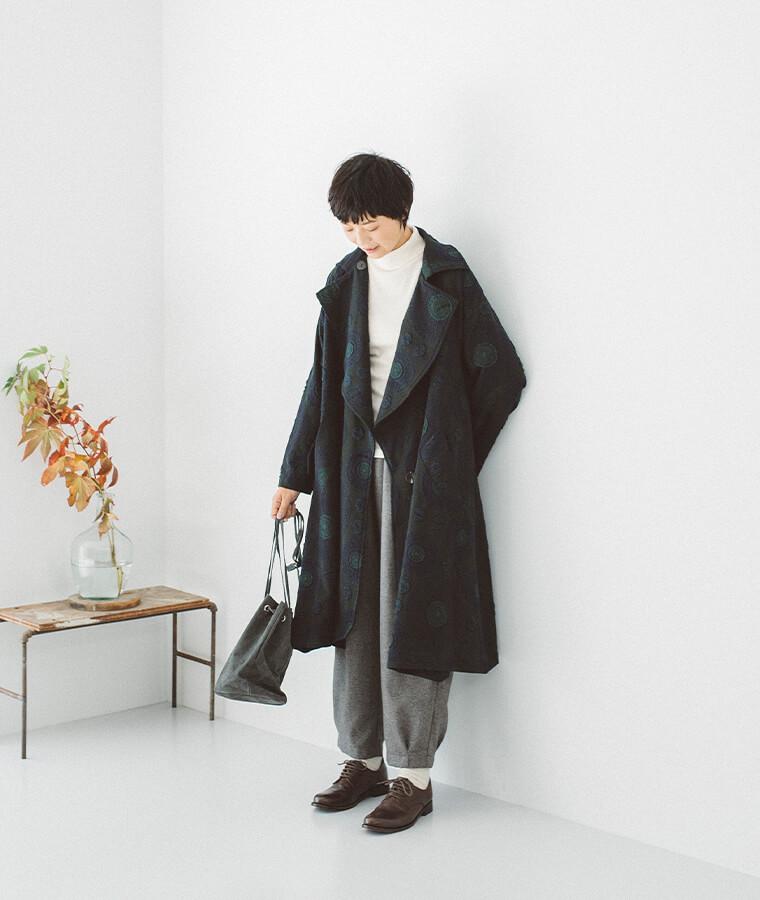 膨れジャカードコートを着た女性