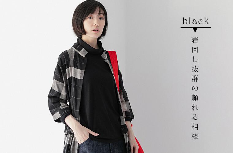 ブラックのタートルネックとチェックのシャツワンピースを着ている女性