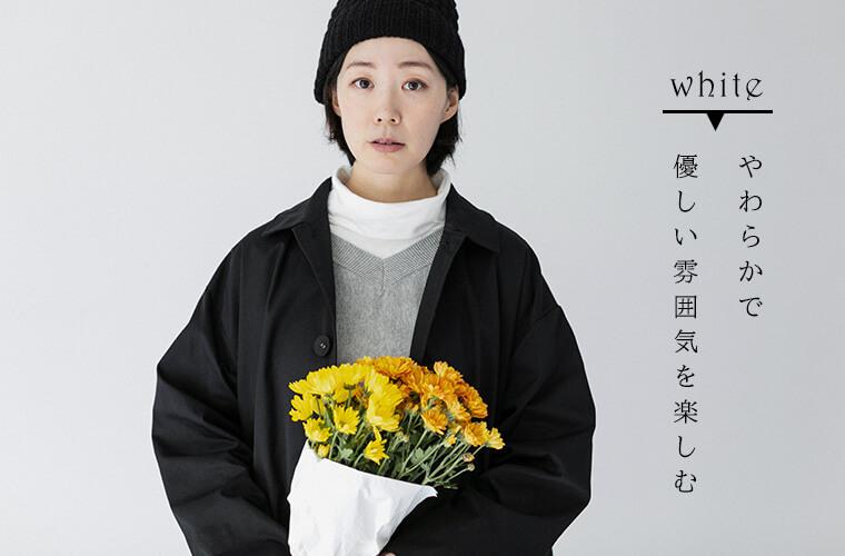 ホワイトのタートルネックとブラックのコートを着ている女性