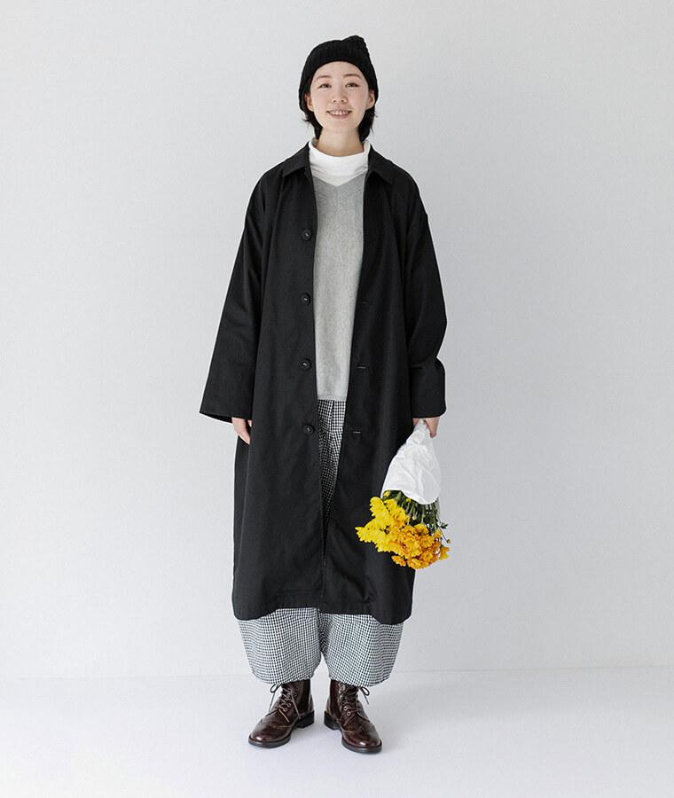 ホワイトのタートルネックとブラックのコートを着てお花を持っている女性