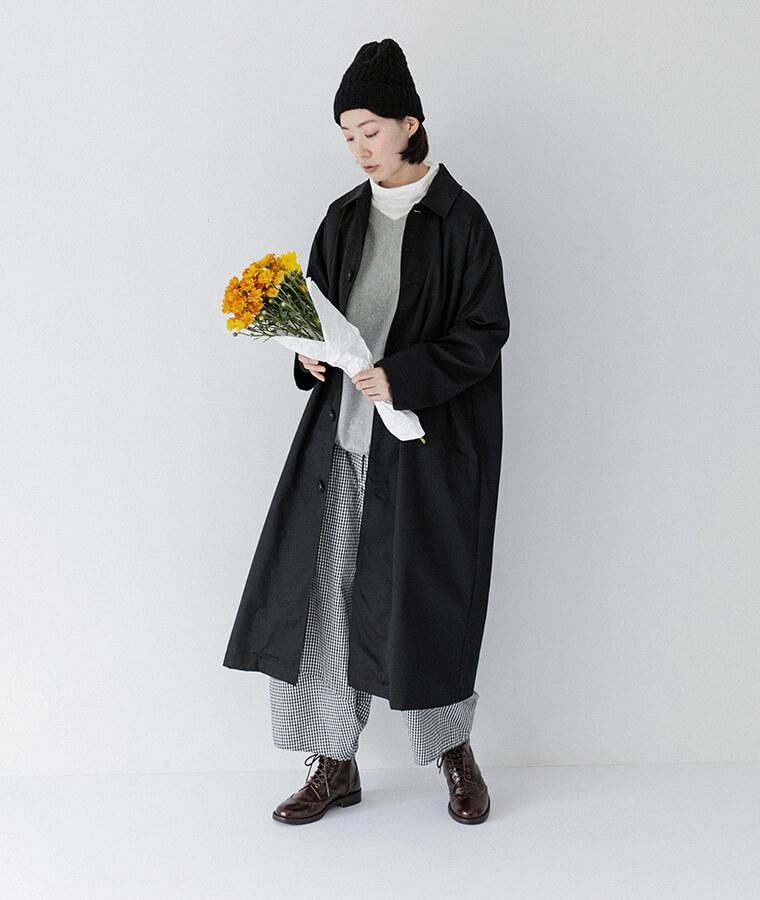 ホワイトのタートルネックとブラックのコートを着てお花を見ている女性