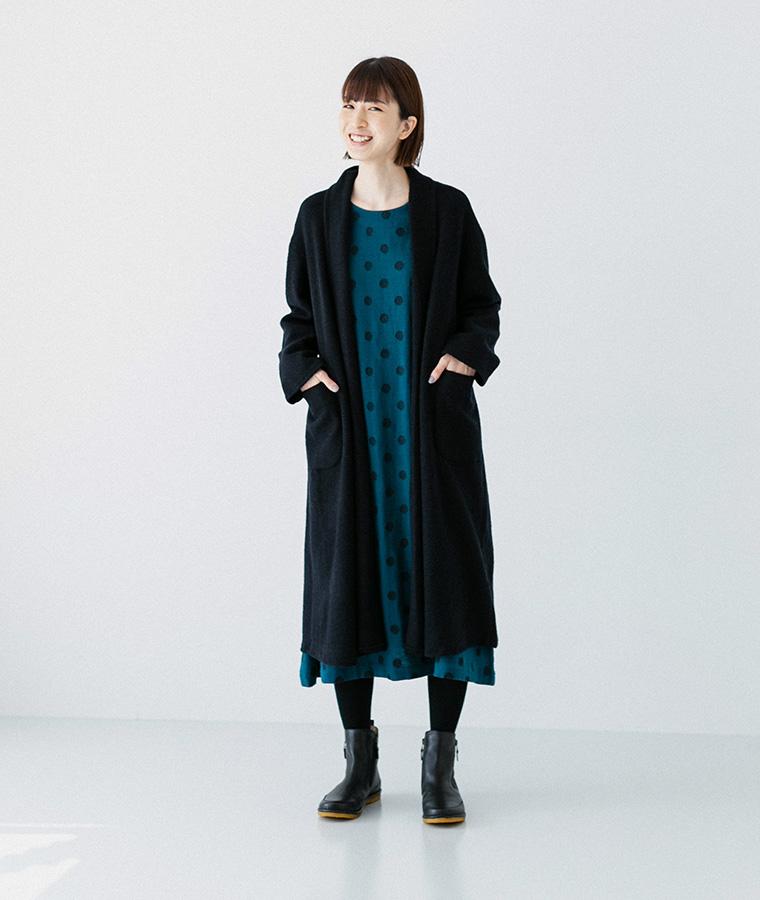 ドットワンピースとブラックのウールコートを着た女性