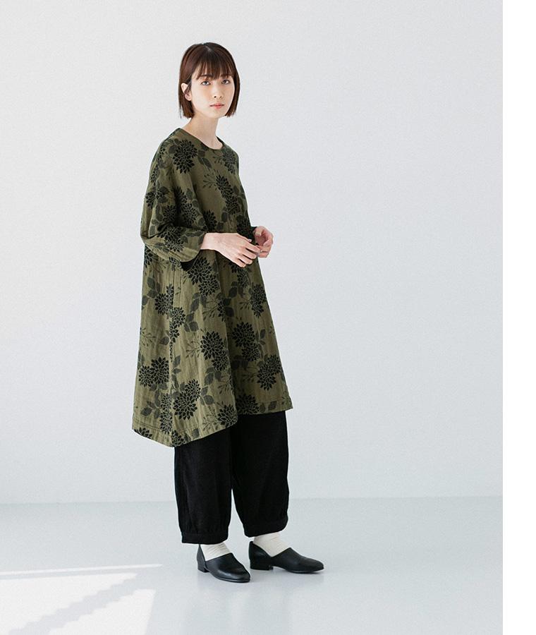 ゴブランワンピースとコーデュロイパンツを着た横向き女性