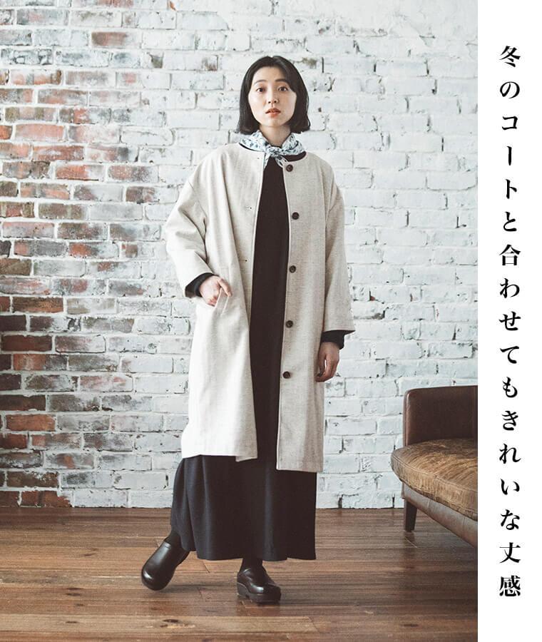 ネイビーのワンピースと白いコートを着た女性