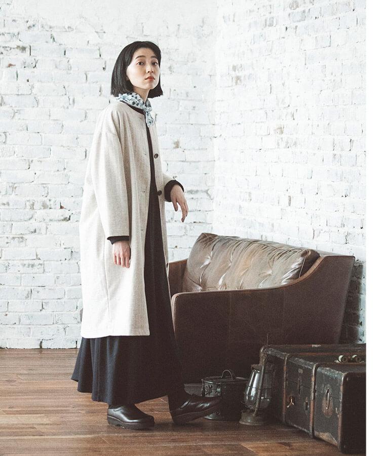 ネイビーのワンピースと白いコートを着た横向き女性