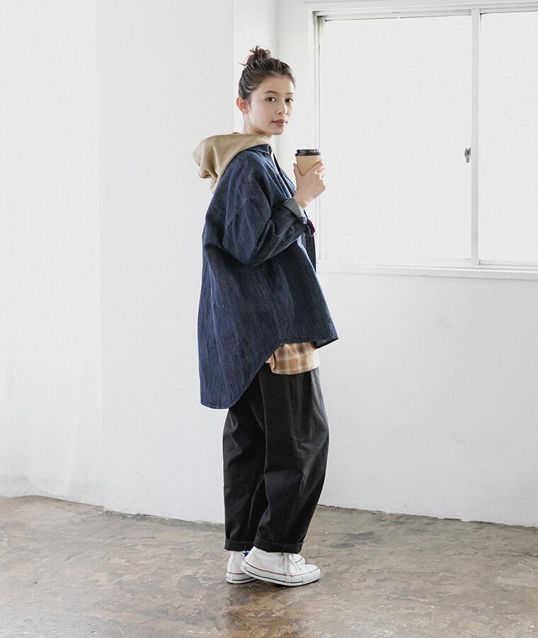 デニムシャツとパンツを履いたコーヒーを持った女性