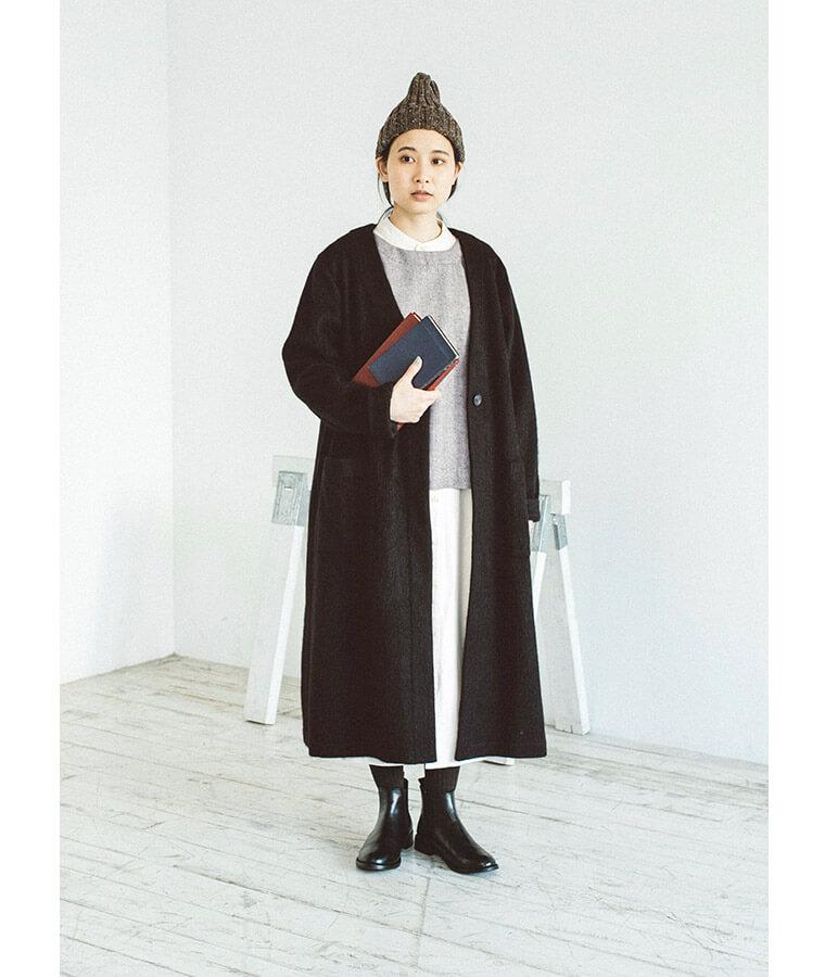 2WAYベストとコートを着た女性