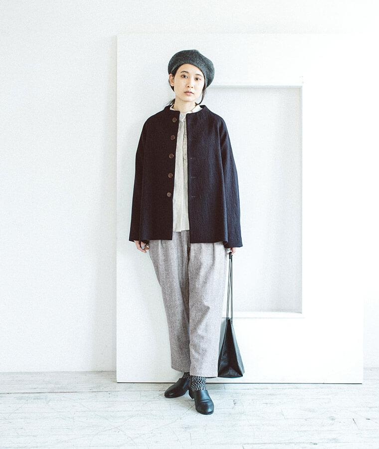 テーパードパンツとコートを羽織った女性