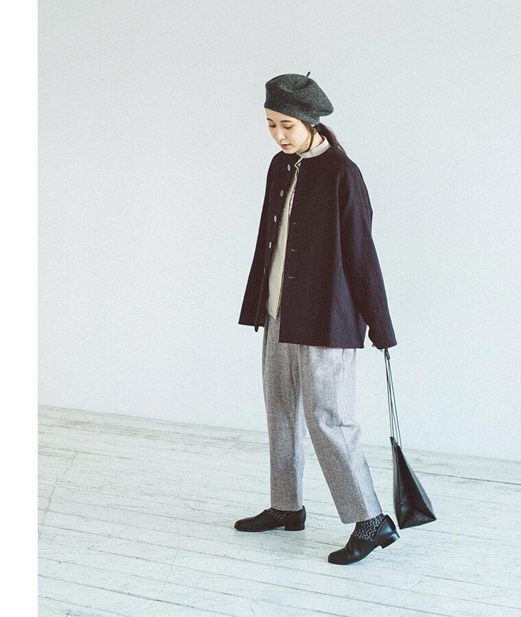 テーパードパンツとコートを羽織った下向き女性