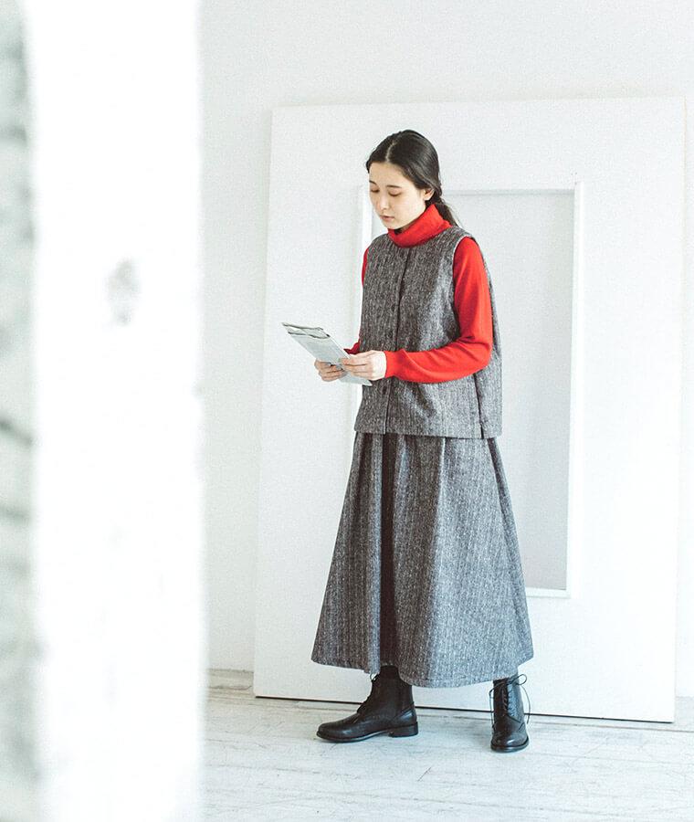 赤いセーターとセットアップを着た下向き女性