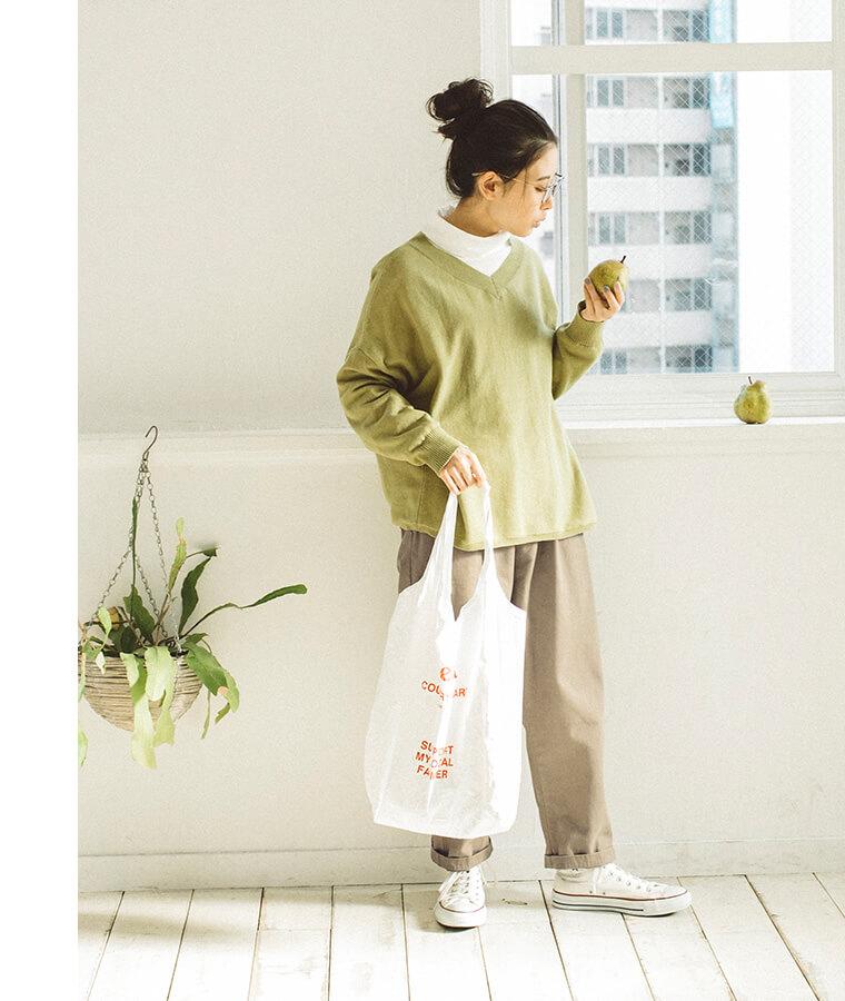 ティーグリーンのニットを着た洋梨を見てる女性