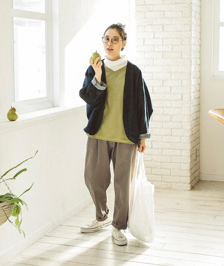 ティーグリーンのニットとデニムジャケットを着た女性
