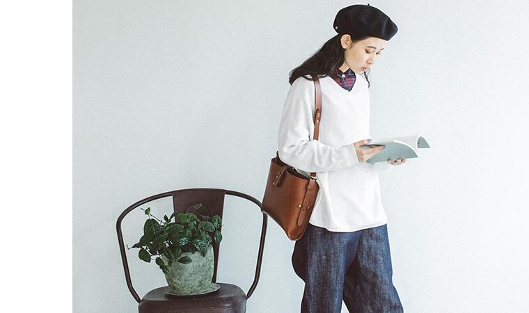 オフホワイトのニットを着た本を読む女性