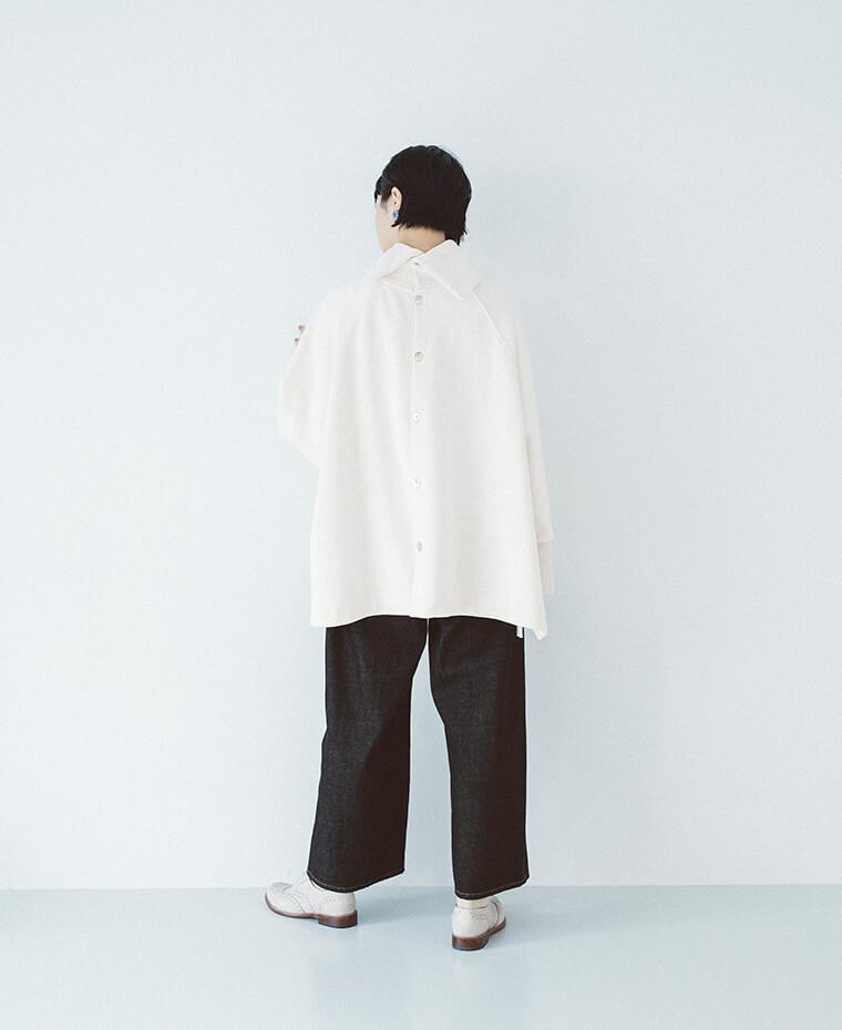 ポンチョ風プルオーバーを着た女性