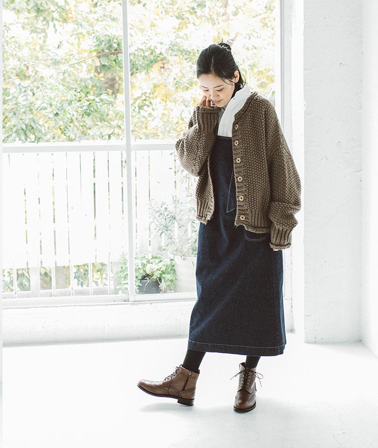 ウィングチップブーツとデニムワンピースを着た女性