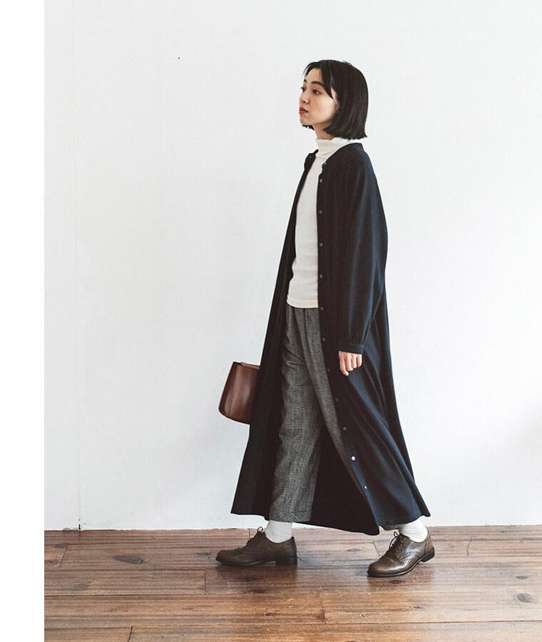メダリオンシューズとロングワンピースを着た女性