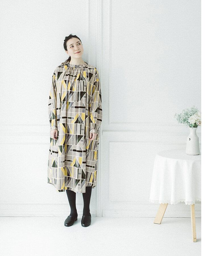 幾何学柄ギャザーワンピースを着た女性