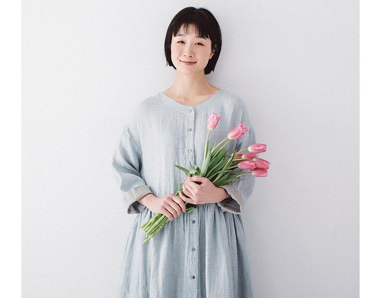 ブルーのワンピースを着たお花を持った女性