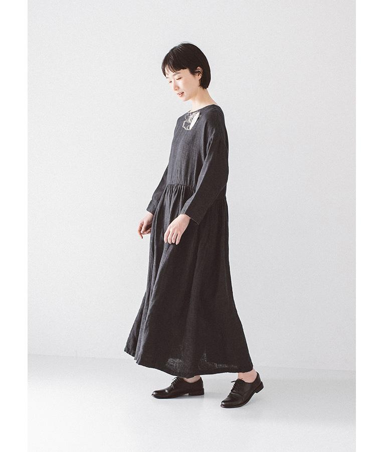 ブラックのワンピースを着た下向き女性