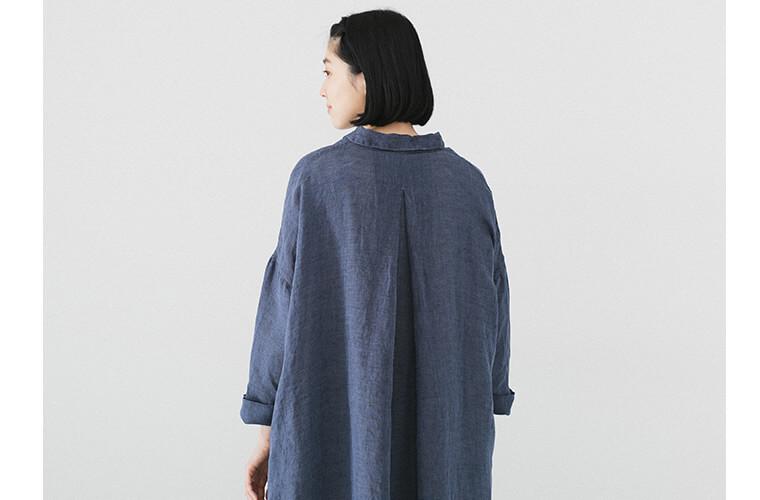 ブルーのシャツワンピースを着た後ろ向き女性