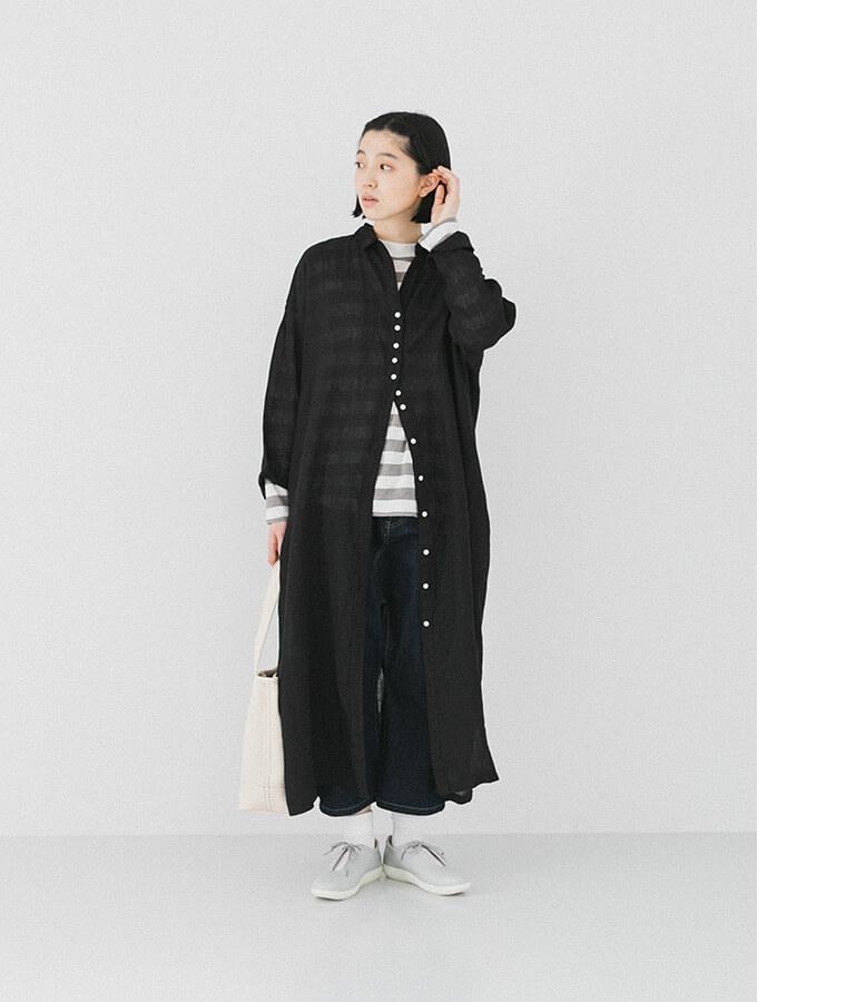 ブラックのシャツワンピースを着た横向き女性