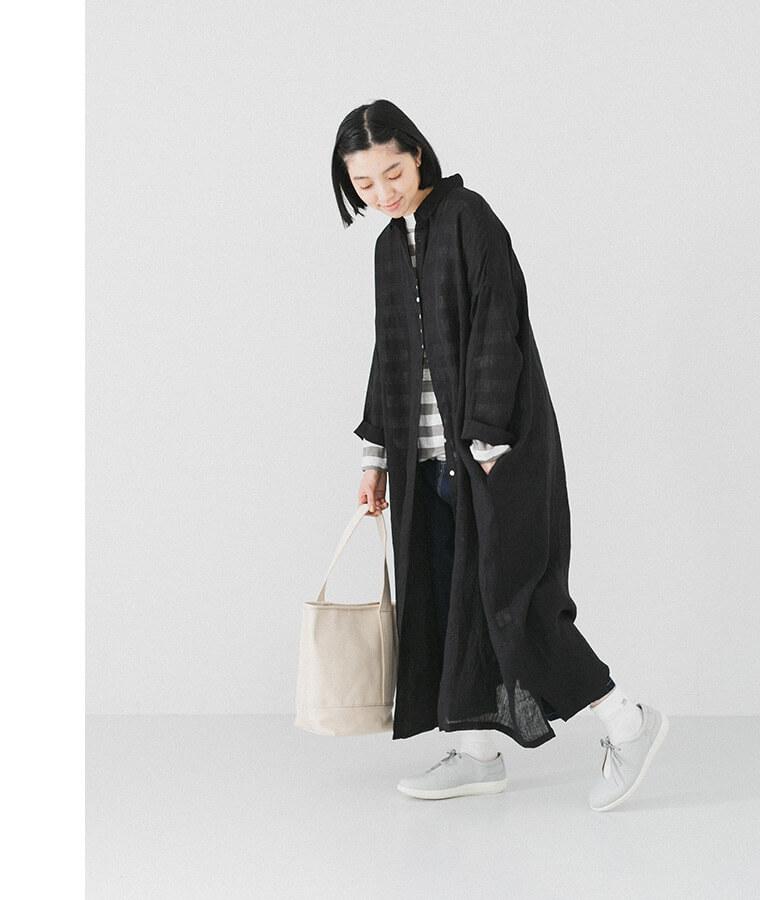 ブラックのシャツワンピースを着た足を上げた女性