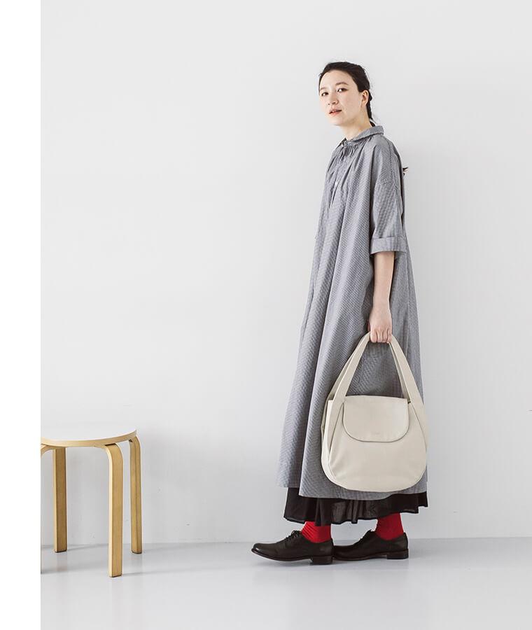 ベージュのバッグ持った横向き女性