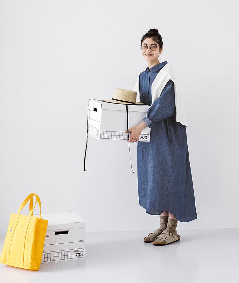 ヴィンテージブルーのシャツワンピースを着た箱を持った女性