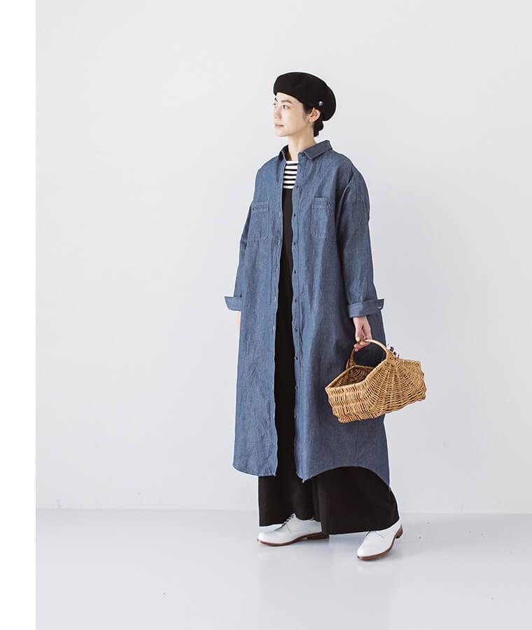 ヴィンテージブルーのシャツワンピースを羽織ったカゴバッグを持った女性