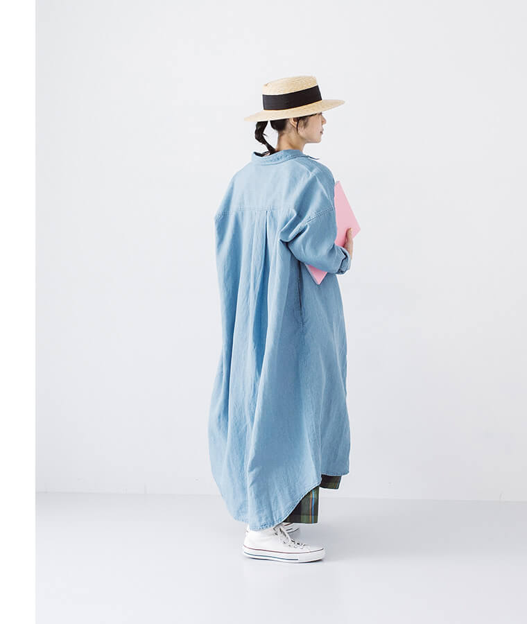 サックスブルーのシャツワンピースを羽織った後ろ向き女性