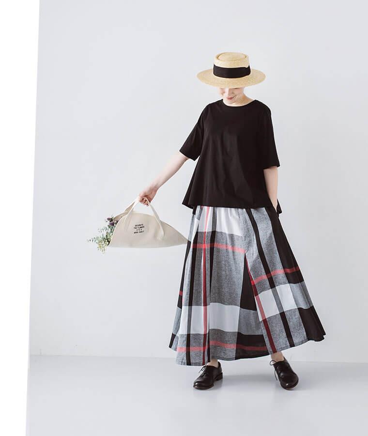 コットンリネンチェックスカートとブラックのトップスを着た下向き女性