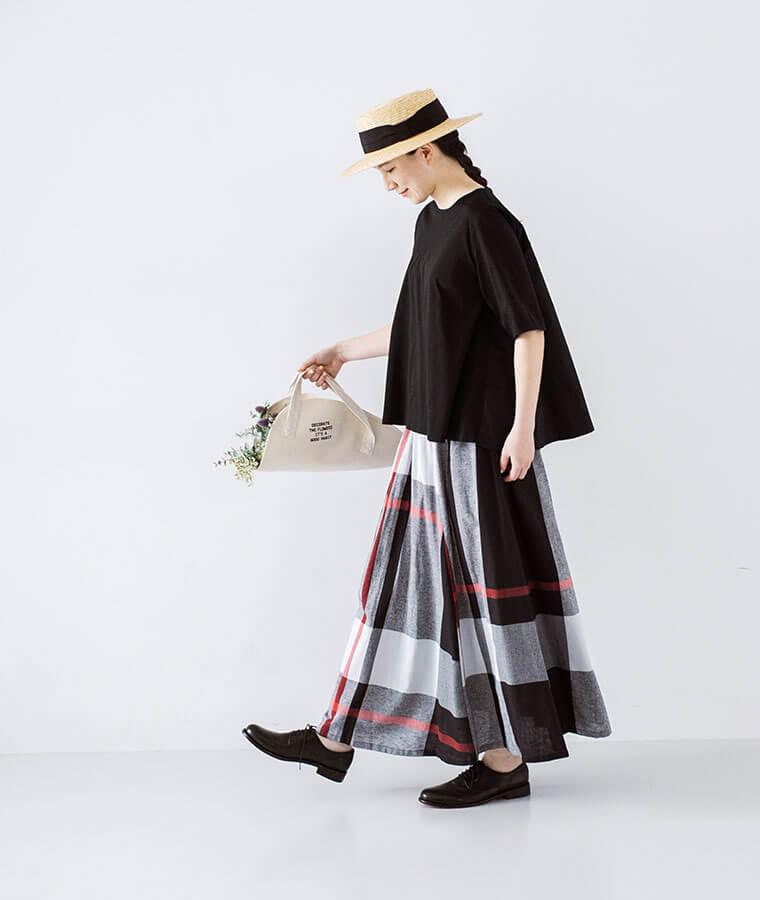コットンリネンチェックスカートとブラックのトップスを着たお花を持った女性