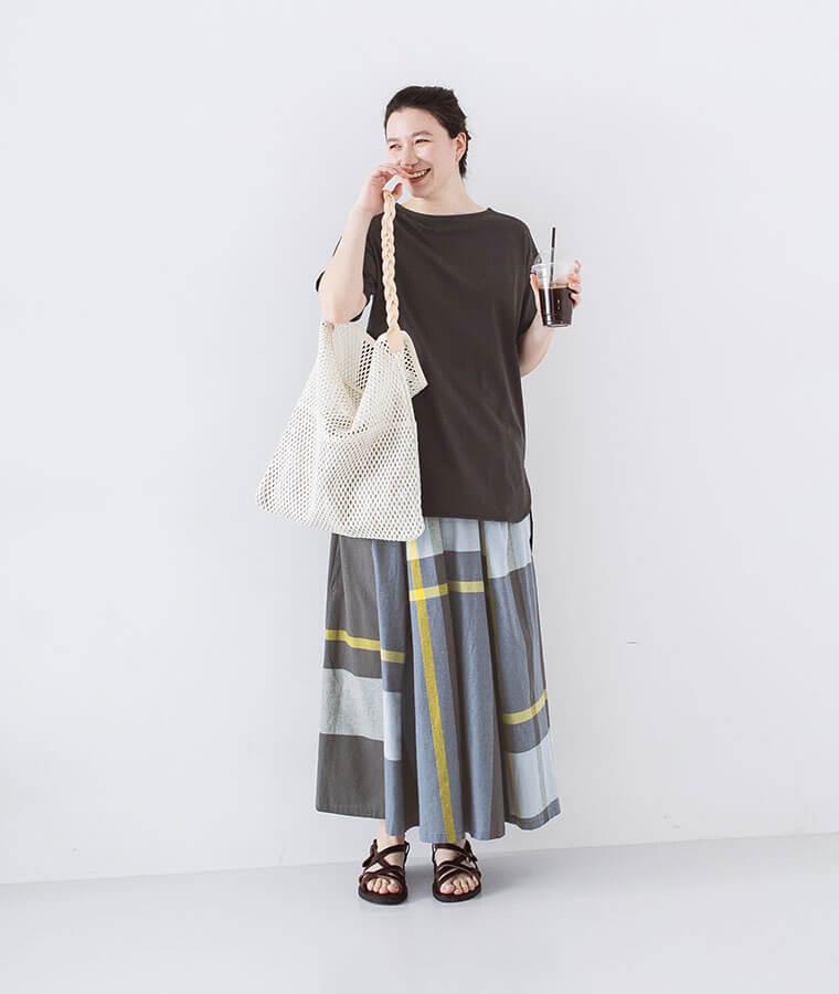 イエローが挿し色のコットンリネンチェックスカートを着たバッグを持った女性