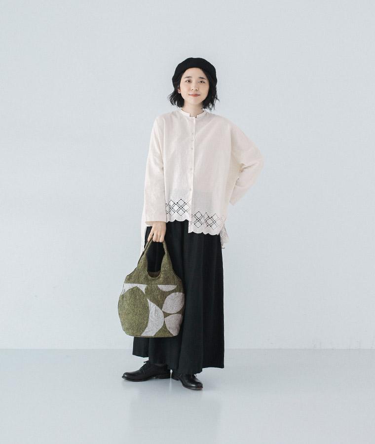 白のブラウスと黒のマキシパンツを合わせたモノトーンコーディネートにTOMOO(トモオ)/【新作】葉の影をイメージしたバッグを持って